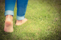 Low section of woman walking on grassy landscape Royalty Free Stock Photography