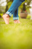Low section of woman walking on green grass Royalty Free Stock Photography