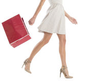 Low Section Of Woman Walking With Shopping Bag. Low section of young woman walking with shopping bag isolated over white background Stock Image