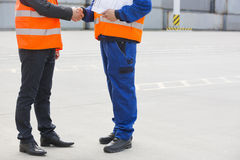 Low section of workers shaking hands in shipping yard Stock Photography