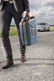 Low section of young businessman carrying gas can with broken car in background at countryside Royalty Free Stock Images