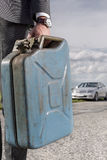Low section of young businessman carrying gasoline can with broken car in background at countryside Stock Photos