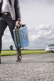 Low section of young businessman carrying gasoline can with broken car in background at countryside Stock Photography
