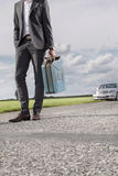 Low section of young businessman carrying petrol can with broken car in background at countryside Stock Image
