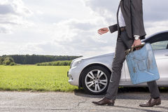 Low section of young businessman with gas can walking by broken down car at countryside Royalty Free Stock Images