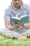 Low section of young man reading book on grass Stock Photos