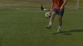 Football player juggling soccer ball on the pitch stock footage