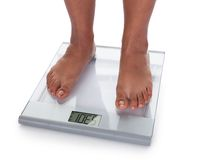 Low section of a young on a weighing scale Royalty Free Stock Photography