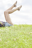 Low section of young woman with feet up lying on grass against sky Stock Photography