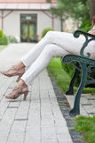 Low section of young woman with high heels sitting on park bench royalty free stock image
