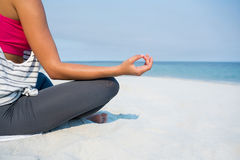 Low section of young woman meditating at beach Royalty Free Stock Images