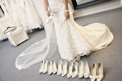 Low section of young woman standing with variety of footwear in bridal boutique stock photography