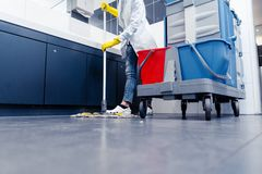 Low shot of cleaning lady mopping the floor in restroom. Beside her trolley royalty free stock photo