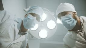 Low shot of doctor and nurse looking into a camera on patient. Low shot of doctor and nurse looking into a camera. Point of view of patient. 4K stock footage