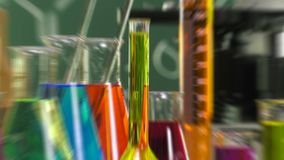 Low speed Zoom in on a bottle filled with yellow liquid. Ambiance performed with various laboratory containers and a microscope on green chalk board background stock footage