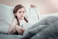 Low-spirited little female taking serviette. Do not cry. Serious kid being in her bed and holding paper box on knees while looking forward Stock Photos