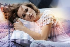 Melancholy woman spending time at home. Low spirited. Upset female keeping head on the pillow and wrinkling forehead while being deep in thoughts Stock Photos