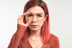 Low-spirited young student frowns after receiving a bad grade for the exam. Beautiful young woman holding glasses stock photo