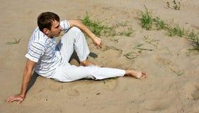Low spirits man. Sitting on the sand Stock Image