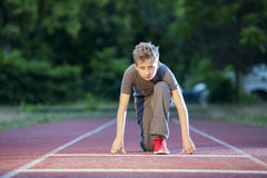 Low start of teen boy. Deep frontal full-body view looking a young male teenagers in low-start position on a tartan track in the camera Stock Photo