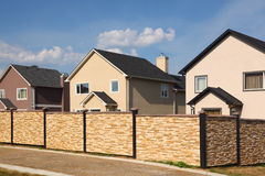Low stone fence on background of new cottages. Royalty Free Stock Image