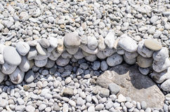 Low Stone Wall on Pebble Beach Stock Image