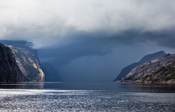 Low storm clouds. Low dark storm clouds coming in over the calm waters of a Norwegian fjord Royalty Free Stock Photo