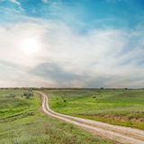 Low sun in clouds over road in green meadow Royalty Free Stock Photography