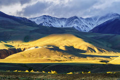 Low sun light pattern on hill and snow covered mountain Royalty Free Stock Photo