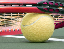 Low tennis ball and racket close up. A close up of a tennis ball sitting on a tennis court under a racket Stock Photography