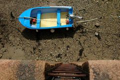 Low Tide. A bright blue fishing boat sits below the quay side at low tide Royalty Free Stock Photos