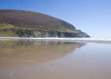 Low tide on beach. Scenic view of cliffs reflecting on picturesque deserted beach at low tide Royalty Free Stock Photo