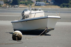 Low tide boat Stock Images