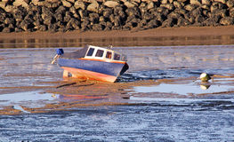Low tide boat on sand Stock Images