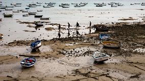 Low tide boats of ocean. Atlantic Ocean scene during low tide with boats and silhouette of people in Cadiz, Andalusia, Spain Stock Images