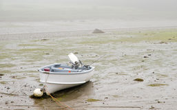 Low tide in fog. A view of a small boat grounded on a Maine tidewater mudflat in morning fog at low tide Royalty Free Stock Photo
