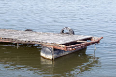 Low tide on the lake and a wooden dock.  Stock Photography