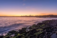 Dawn begins from Crissy Field Beach. During low tide it is possible to access the rocky beach and photograph the iconic skyline at sunrise, as it casts its royalty free stock photos