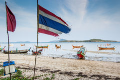Low tide at Rawai Beach in Phuket, Thailand. RAWAI BEACH, PHUKET, THAILAND - APRIL 9, 2013: Thai flag and long-tail boats at low tide on Rawai Beach in Phuket Royalty Free Stock Photos