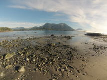 Low tide with rocks, sand and mountain background Royalty Free Stock Image