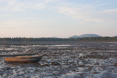Low Tide. Row boat stranded by receding tide royalty free stock image