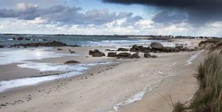 Low tide. Sandy and rocky coastline in France in low tide, with village on the horizon Stock Image