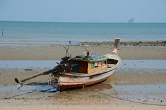 Low tide. Small fishing boat at the low tide beach Stock Photos