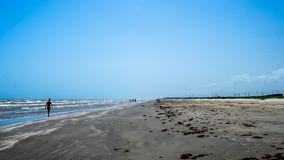 Low Tide Stroll Along The Beach. People wade in the surf at the beach in the morning stock photo