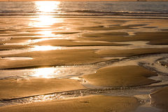 Low tide at sunset. Water flowing out to sea at low tide stock photo
