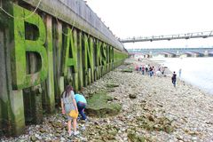 Low tide in the Thames. People walking on the banks of the Thames and looking for bargains Royalty Free Stock Photo