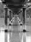 Low tide under a timber pedestrian bridge.  Stock Photos