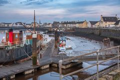 Low Tides at Irvine harbour and Looking Along Harbour Street to. Some small boats at the old jetty in Harbour Street Irvine and looking along to the town of royalty free stock photo