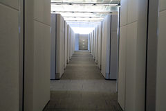 Low View of Clean modern office hallway of cubicle. Focus on end filing cabinet after looking down a modern clean hallway in an office environment. Low view Stock Images