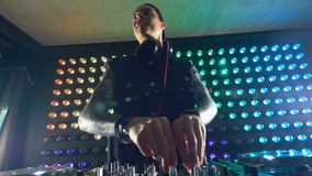 A low view on a DJ at work. A DJ works at a mixer and nods to the music
